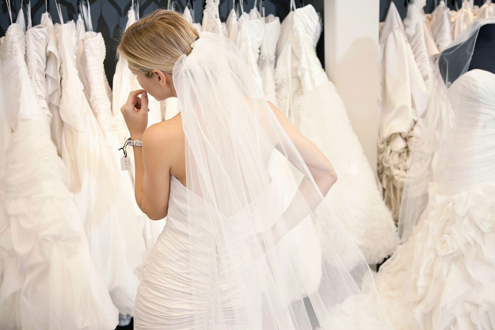 בחורה בשמלת כלה מסתכלת על שמלות כלה